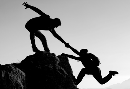 Photo noir et blanc d'un alpiniste aidant un autre alpiniste à gravir un sommet