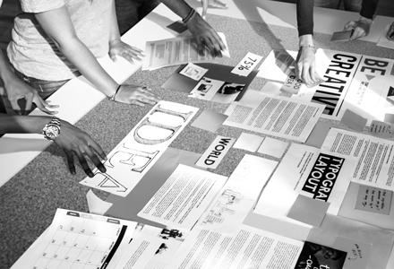 photo noir et blanc de personnes travaillant autour d'un tableau d'inspiration façon brainstorming
